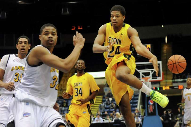 Siena's Lavon Long, right, loses the ball as a foul is called on Canisius' Dominique Raney, center,