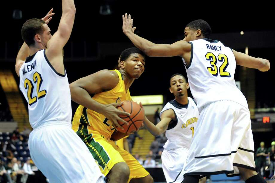 Siena's Lavon Long, center, is blocked in as Canisius' Phil Valenti, left, Zach Lewis, second from right, and Dominique Raney defend in their second-round basketball game of the MAAC Tournament on Saturday, March 8, 2014, at MassMutual Center in Springfield, Mass. (Cindy Schultz / Times Union) Photo: Cindy Schultz / 00026001A