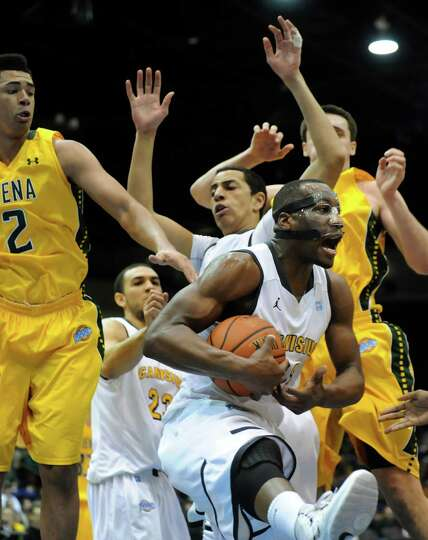 Canisius' Chris Manhertz, center, wins the rebound in their second-round basketball game of the MAAC