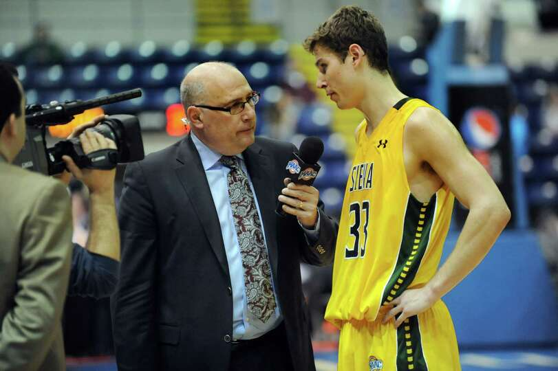 Former Siena coach Mitch Buonaguro, center, interviews Siena's Rob Poole at halftime for ESPN3 durin