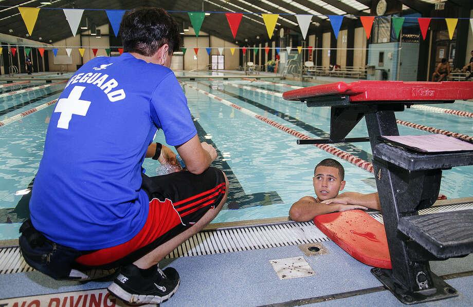 Joel Vargas, 16, listens to swimming tips from four-year lifeguard Sergio Zavala at the lifeguard recruitment party. Photo: Alma E. Hernandez / For The San Antonio Express-News