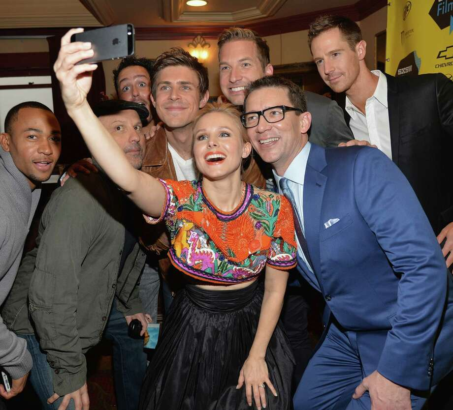 """Actress Kristen Bell poses for a selfie with cast members Percy Daggs (from left), Enrico Colantoni, Chris Lowell, Ryan Hansen, Jason Dohring and director Rob Thomas at the """"Veronica Mars"""" premiere. Photo: Michael Buckner / Getty Images / 2014 Getty Images"""