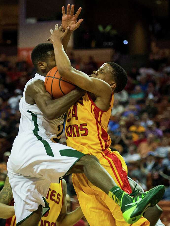 Yates guard Jacob Young (24) fights for control of a rebound against Dallas Madison guard Le'Braun Armstrong during the second half. Photo: Smiley N. Pool, Staff / © 2014  Houston Chronicle