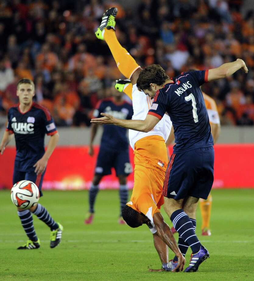The Dynamo's Omar Cummings, left, is upended by the Revolution's Patrick Mullins during the first half. Cummings had the last laugh with the final goal. Photo: Eric Christian Smith, Freelance