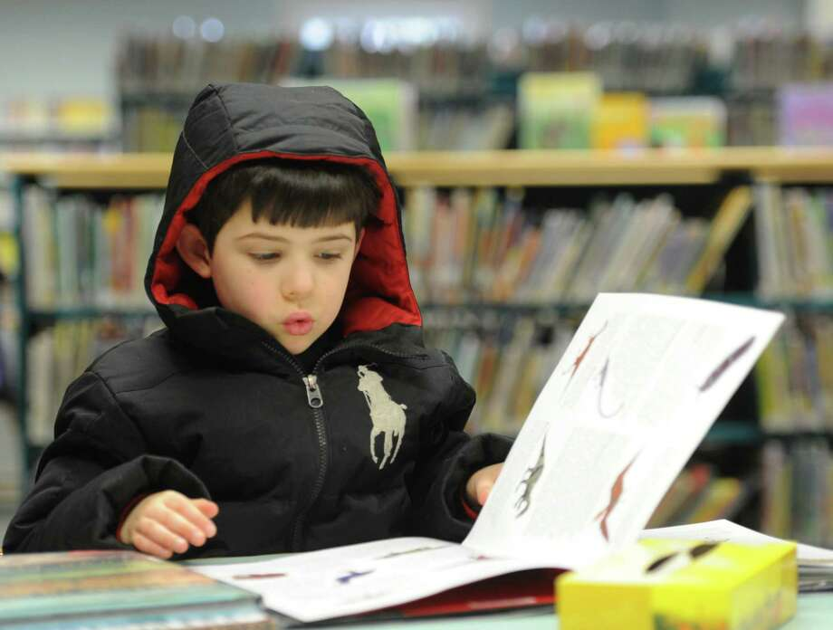 Theo Anderson, 6, of Newtown, reads a book during the re-opening of the C.H. Booth Library in Newtown on Saturday.  The library was closed for 8 weeks after a frozen sprinkler pipe burst, causing extensive water damage throughout the library. Photo: Tyler Sizemore / The News-Times