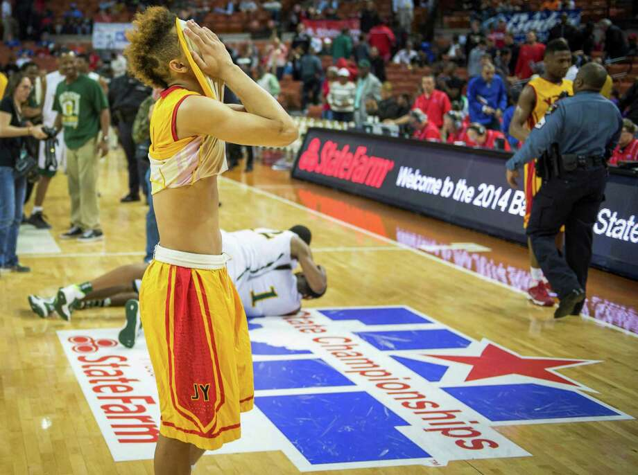 Yates guard Milton Jackson can't watch as Dallas Madison's Johnathan Turner (1) and Cameron Bryant (2) celebrate following their 82-70 victory over the Lions in the Class 3A state championship game in Austin. Photo: Smiley N. Pool, Staff / © 2014  Houston Chronicle
