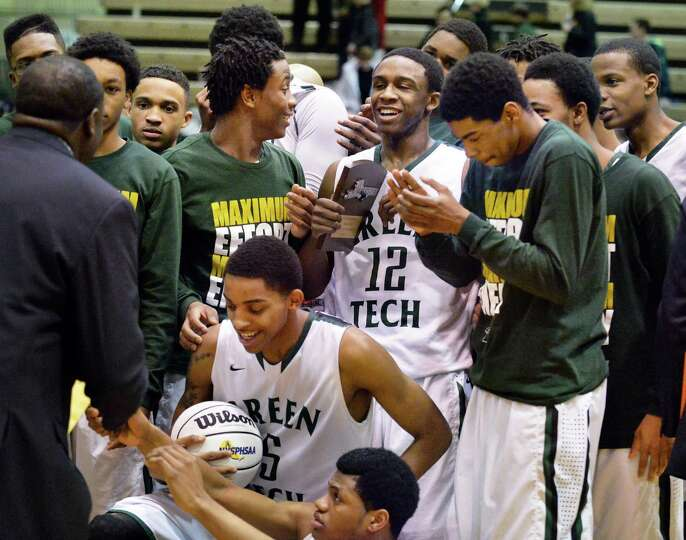Green Tech head coach Jamil Hood, Sr. and players celebrate their victory in the Class AA boys' regi