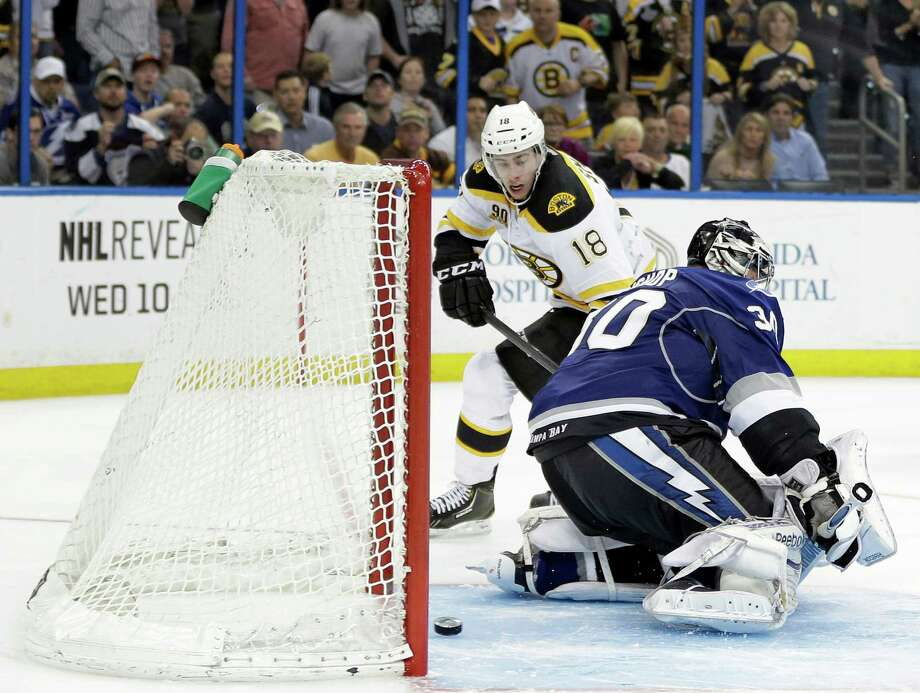 Boston Bruins right wing Reilly Smith (18) scores past Tampa Bay Lightning goalie Ben Bishop in a shoot out during an NHL hockey game Saturday, March 8, 2014, in Tampa, Fla. The Bruins won the game 4-3. (AP Photo/Chris O'Meara)  ORG XMIT: TPA111 Photo: Chris O'Meara / AP
