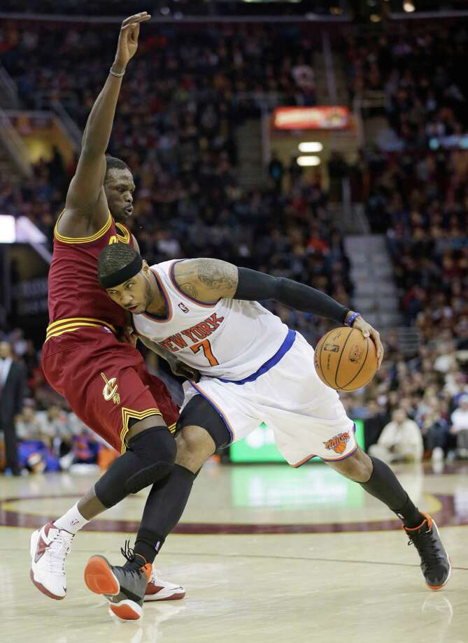 New York Knicks' Carmelo Anthony, right, drives against Cleveland Cavaliers' Luol Deng during an NBA basketball game Saturday, March 8, 2014, in Cleveland. Anthony scored a team-high 26 points in New York's 107-97 win over Cleveland. (AP Photo/Tony Dejak) ORG XMIT: OHTD107 Photo: Tony Dejak / AP