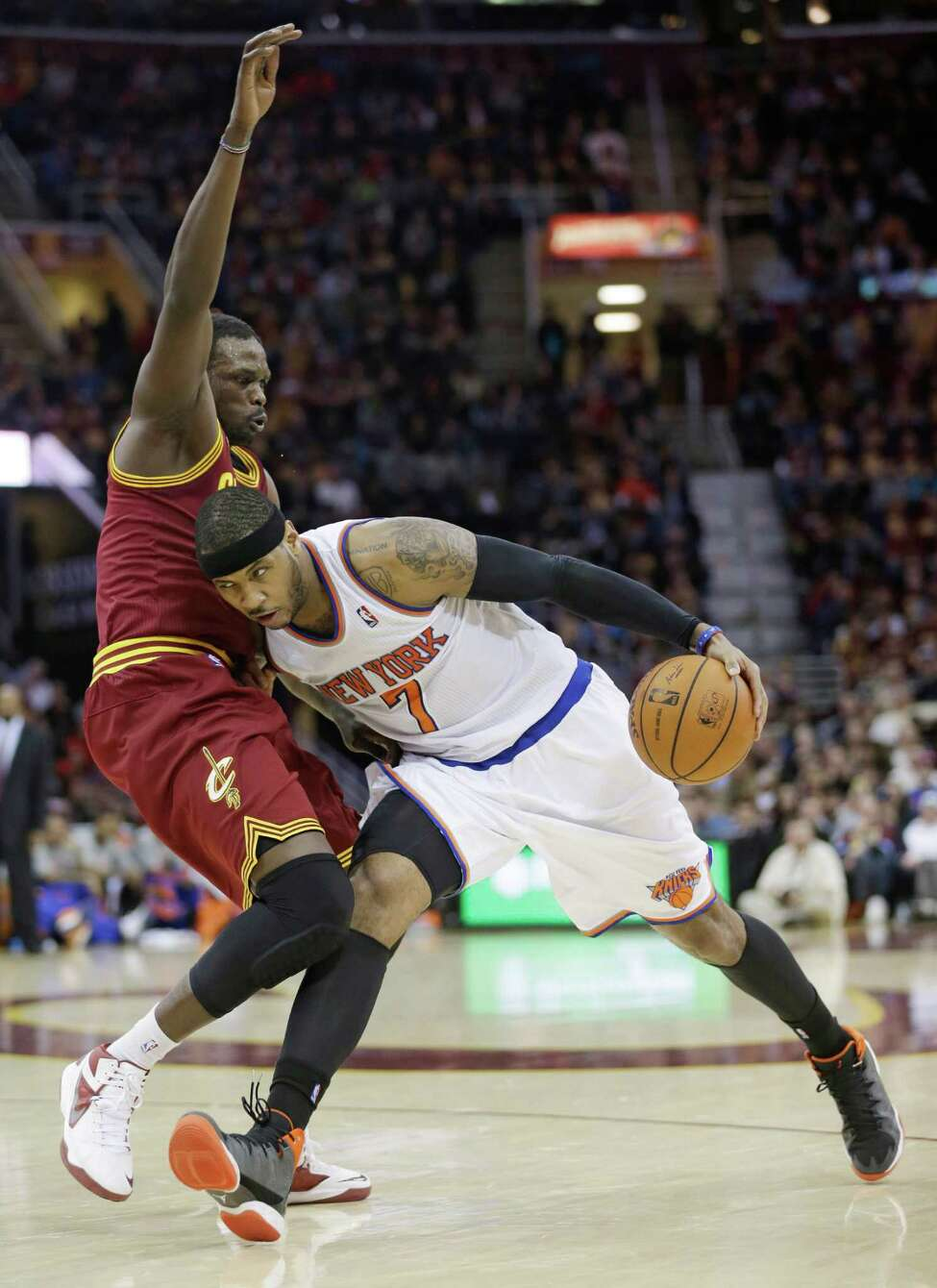 New York Knicks' Carmelo Anthony, right, drives against Cleveland Cavaliers' Luol Deng during an NBA basketball game Saturday, March 8, 2014, in Cleveland. Anthony scored a team-high 26 points in New York's 107-97 win over Cleveland. (AP Photo/Tony Dejak) ORG XMIT: OHTD107