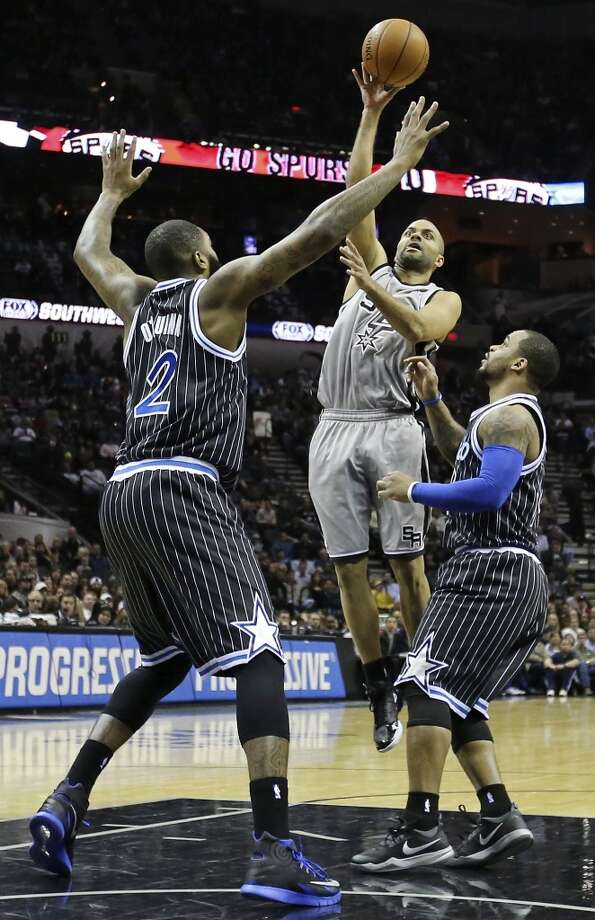 San Antonio Spurs' Tony Parker shoots between Orlando Magic's Kyle O'Quinn (left) and Andrew Nicholson during first half action Saturday March 8, 2014 at the AT&T Center. Photo: San Antonio Express-News