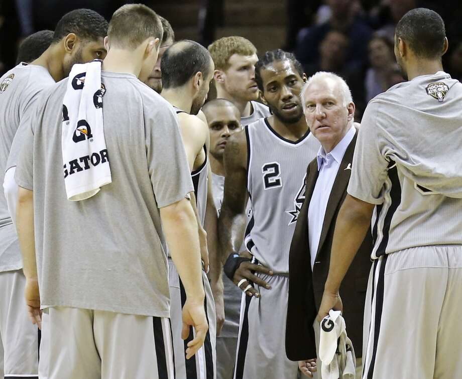 San Antonio Spurs head coach Gregg Popovich (center) talks with the team during second half action against the Orlando Magic Saturday March 8, 2014 at the AT&T Center. The Spurs won 121-112. Photo: San Antonio Express-News