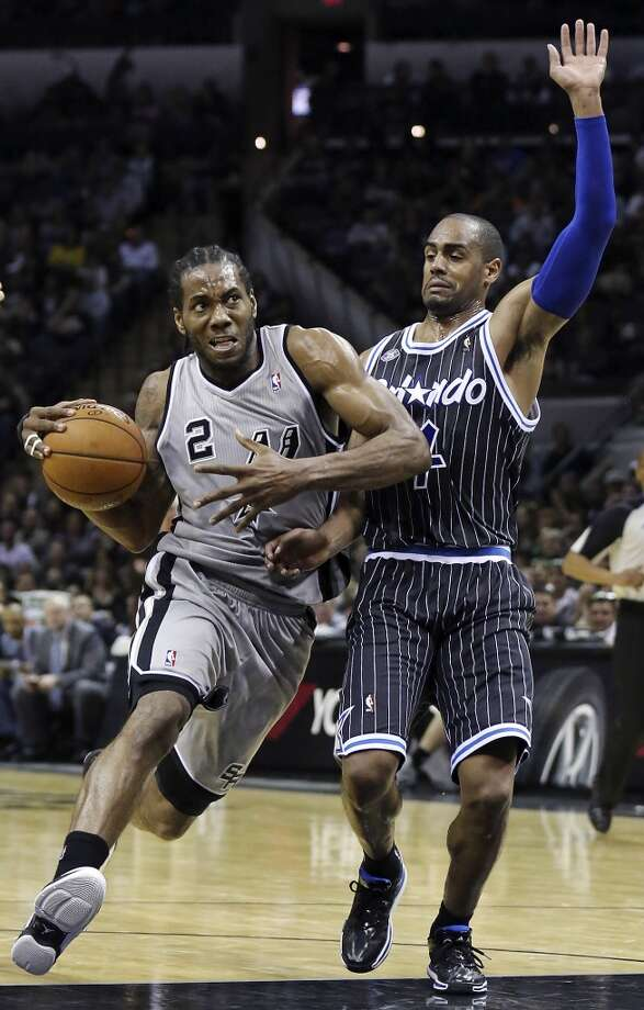 San Antonio Spurs' Kawhi Leonard looks for room around Orlando Magic's Arron Afflalo during second half action Saturday March 8, 2014 at the AT&T Center. The Spurs won 121-112. Photo: San Antonio Express-News