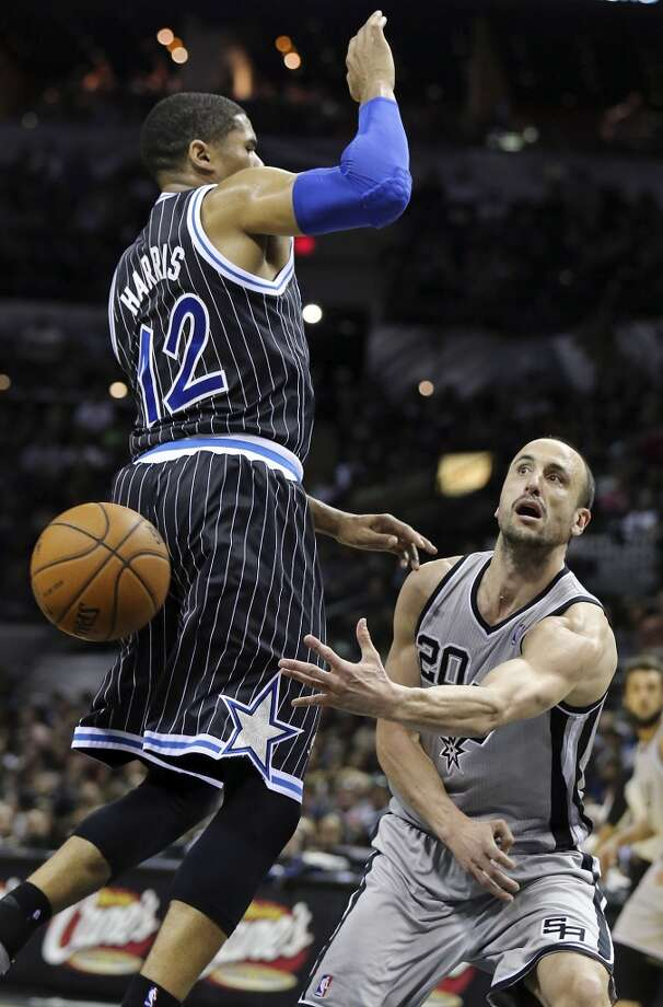 San Antonio Spurs' Manu Ginobili passes around Orlando Magic's Tobias Harris during second half action Saturday March 8, 2014 at the AT&T Center. The Spurs won 121-112. Photo: San Antonio Express-News