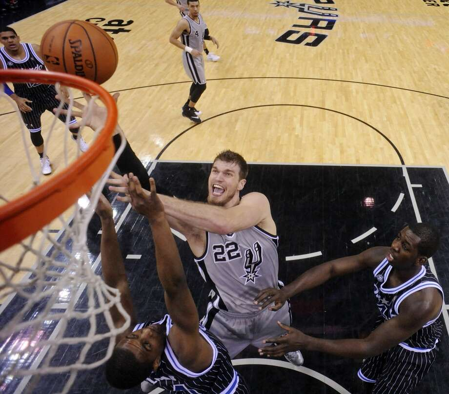 San Antonio Spurs' Tiago Splitter shoots between Orlando Magic's Doron Lamb (left) and Andrew Nicholson during second half action Saturday March 8, 2014 at the AT&T Center. The Spurs won 121-112. Photo: San Antonio Express-News