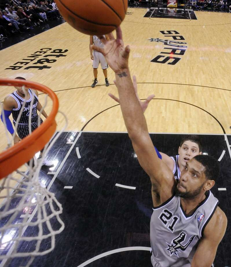 San Antonio Spurs' Tim Duncan shoots around Orlando Magic's Nikola Vucevic during second half action Saturday March 8, 2014 at the AT&T Center. The Spurs won 121-112. Photo: San Antonio Express-News