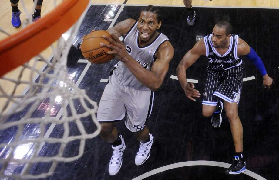 San Antonio Spurs' Kawhi Leonard drives to the basket around Orlando Magic's Arron Afflalo during second half action Saturday March 8, 2014 at the AT&T Center. The Spurs won 121-112. Photo: San Antonio Express-News