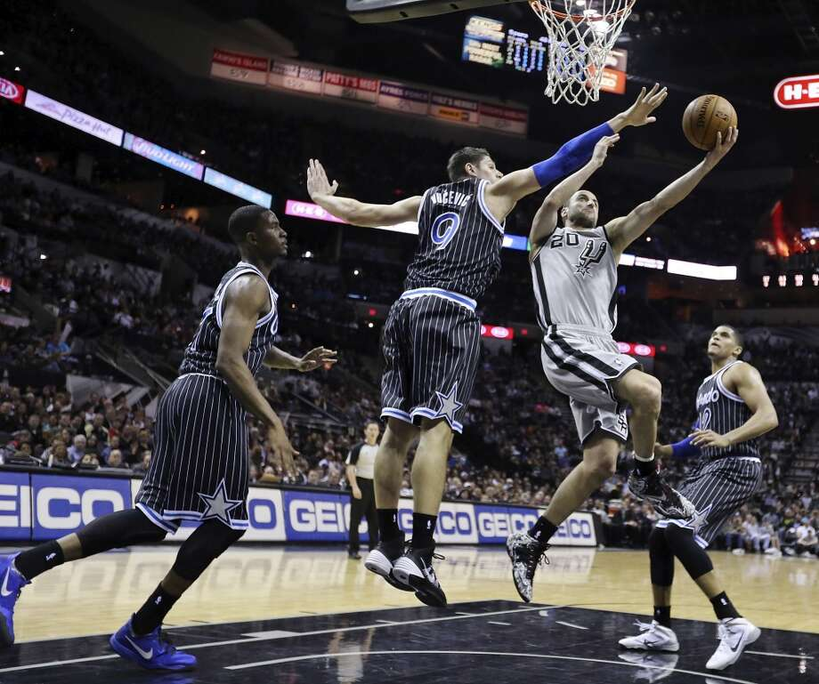 San Antonio Spurs' Manu Ginobili shoots between Orlando Magic's Maurice Harkless (from left), Nikola Vucevic, and Tobias Harris during first half action Saturday March 8, 2014 at the AT&T Center. Photo: San Antonio Express-News