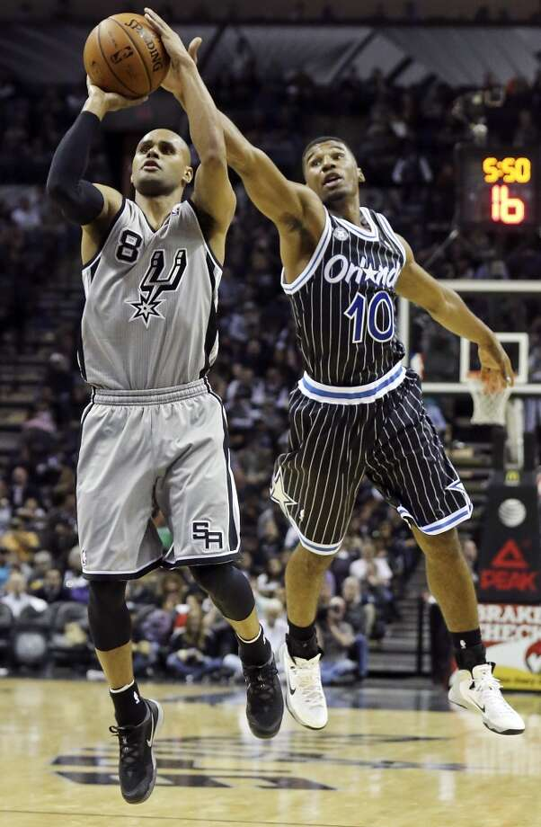 San Antonio Spurs' Patty Mills shoots around Orlando Magic's Ronnie Price during first half action Saturday March 8, 2014 at the AT&T Center. Photo: San Antonio Express-News