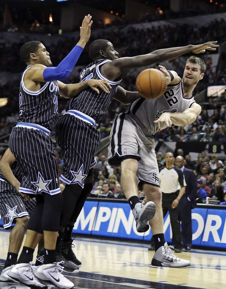 San Antonio Spurs' Tiago Splitter passes around Orlando Magic's Tobias Harris (left) and Andrew Nicholson during second half action Saturday March 8, 2014 at the AT&T Center. The Spurs won 121-112. Photo: San Antonio Express-News