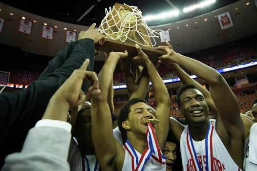 Galena Park North Shore players, including guard Marion Roy, center, celebrate with their state championship trophy after defeating Converse Judson in the boys' UIL Class 5A state basketball championship game on Saturday, March 8, 2014, in Austin. Photo: Smiley N. Pool, Houston Chronicle / © 2014  Houston Chronicle
