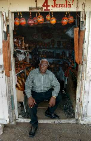 A shop owner sits in his doorway in downtown Cap-Haitien. The man sells trinkets to tourists, which are  rare in this poor region. Photo: Christian Abraham / Connecticut Post