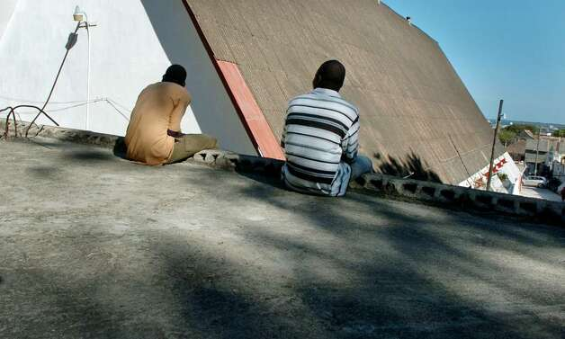 Two former Pierre Toussaint students live on the streets and sleep on the flat cement roof of an old church in downtown Cap-Haitien. Photo: Christian Abraham / Connecticut Post