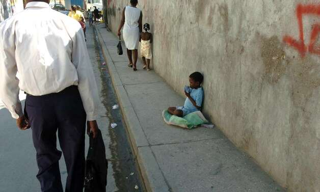 Everyday this little blind boy, sits on a plastic tablecloth leaning against a wall and staring aimlessly at the road as hundreds  of  people pass him climbing the hill on their way to the Justinien Hospital in Cap Haitien. Photo: Christian Abraham / Connecticut Post
