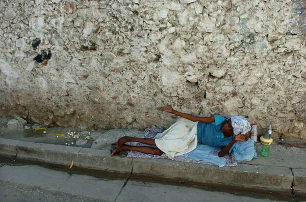 A homeless woman begs for change in downtown Cap-Haitien, where many of its 180,000 residents pack the streets during daylight. Unemployment is the norm and people beg for food, clothes and money. Photo: Christian Abraham / Connecticut Post