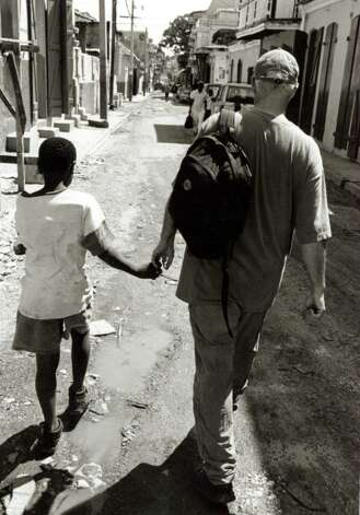Father Paul Carrier walks the streets of Haiti with (then) 10 year old Wilnaud. Photo: Contributed Photo / Connecticut Post Contributed