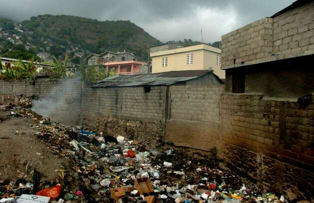 In the streets of downtown Cap-Haitien, garbage collects in a ravine where a pig searches for a meal. Photo: Christian Abraham / Connecticut Post