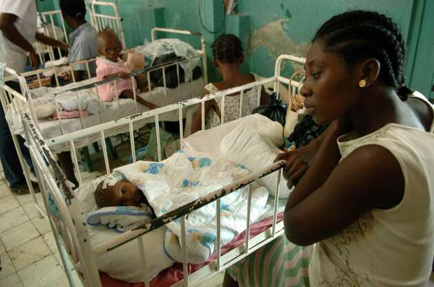 A young woman watches over her sister's three month old baby in the pediatric ward at Justinien Hospital, in downtown Cap Haitien. The mother died while giving birth. Photo: Christian Abraham / Connecticut Post