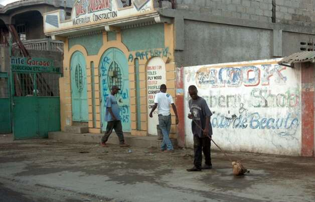 A man works to clean the street in downtown Cap-Haitien in December 2009. Photo: Christian Abraham / Connecticut Post
