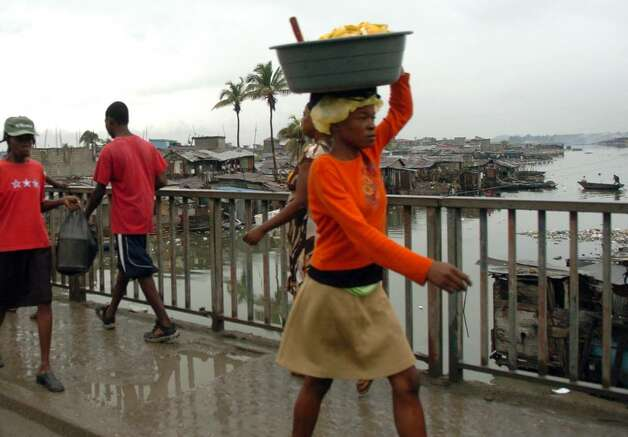 A woman carries a bundle on her head as she crosses the Mapou River bridge in downtown Cap-Haitien, Haiti on December 14, 2009. Photo: Christian Abraham / Connecticut Post