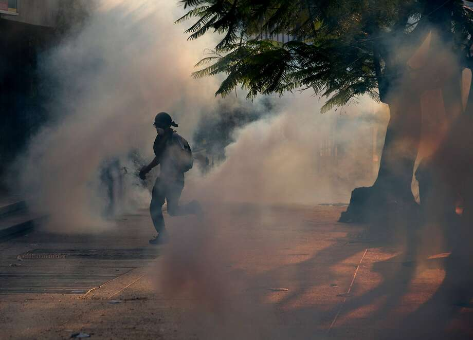 A demonstrator take cover from tear gas fired by Bolivarian National police during clashes with anti-government protesters in Caracas,Venezuela, Saturday, March 8, 2014. The Venezuelan government and opposition appear to have reached a stalemate, in which street protests continue almost daily while the opposition sits out a peace process it calls farcical. (AP Photo/Fernando Llano) Photo: Fernando Llano, Associated Press