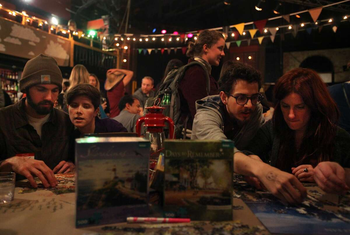 From left, Greg Richardson, 26, Monica Canfield-Lenfest, 33, Anthony Rocco, 27, and Danielle Brandon, 37, work on puzzles during Unplug SF March 7, 2014 at Broadway Studios in North Beach in San Francisco, Calif. The event, which required all attendants to surrender their cellphones and all