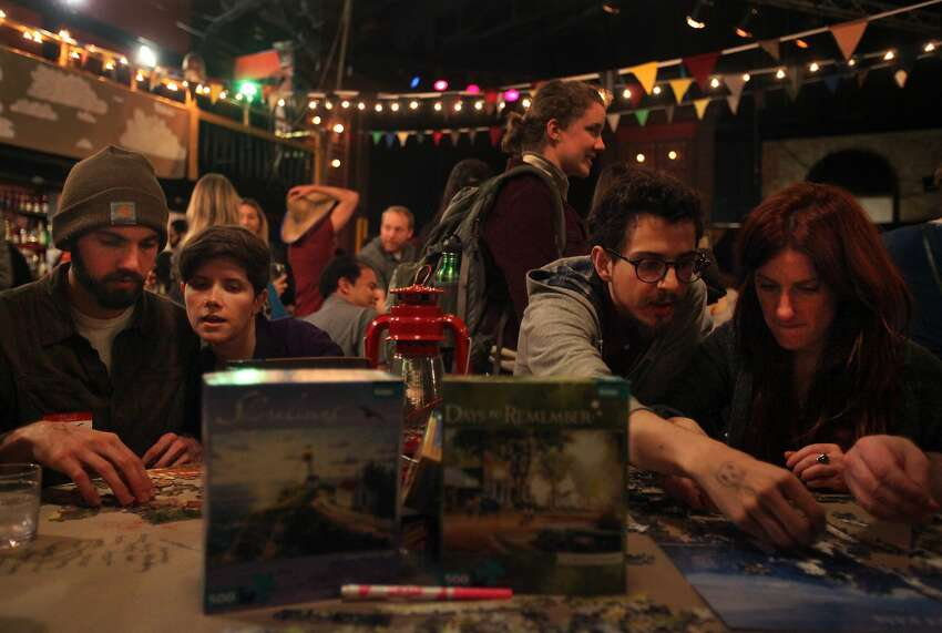 Greg Richardson (left), Monica Canfield-Lenfest, Anthony Rocco and Danielle Brandon work on puzzles at the Unplug SF party at a bar in North Beach.