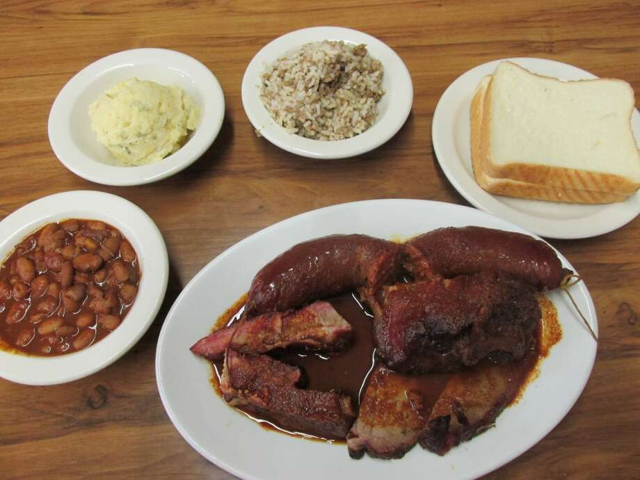 A plate with a homemade link, pork bone, brisket and ribs - plus the sides, including white bread - at Gerard's Barbecue Diner in Beaumont. Photo: Cat5