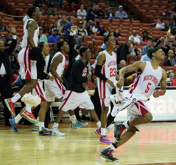 North Shore players, including guard Brandon Green (5) and guard Kerwin Roach (23) race onto the cou