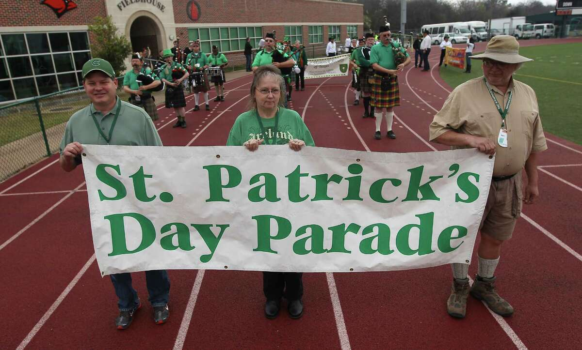Volunteers Phil Burke (from left), Brenda Fernandez and Mark Lawson hold the banner to mark the St. Patrick's Day Parade at the University of the Incarnate Word on Saturday, Mar. 8, 2014.