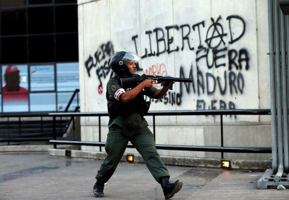 "A Bolivarian National Guard officer points his tear gas grenade launcher at demonstrators during anti-government protests in Caracas, Venezuela, Tuesday, March 4, 2014. The graffiti on the wall reads in Spanish, ""Freedom, Out Maduro Out"". After almost a year after the death of Hugo Chavez, Venezuela has been rocked by weeks of violent protests that the government says have left several dead. President Maduro appears ready to use Chavez's almost mythical status to steady his rule as protesters refuse to leave the streets. Photo: Fernando Llano, AP / AP2014"
