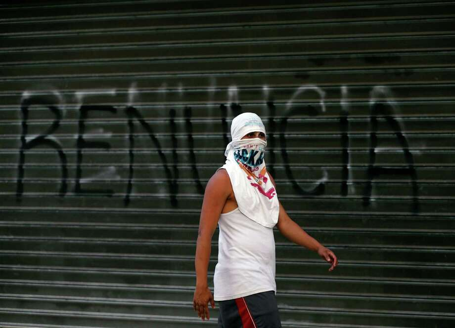 "A demonstrator walks passes next to a graffiti that reads in Spanish ""Resign"",  during anti-government protests in Caracas, Venezuela, Tuesday, March 4, 2014. After almost a year after the death of Hugo Chavez, Venezuela has been rocked by weeks of violent protests that the government says have left several dead. Photo: Fernando Llano, AP / AP2014"