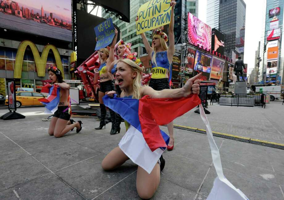 Female activist members of FEMEN rip Russian flags during their anti-Putin, pro-Ukraine demonstration in New York's Times Square, Thursday, March 6, 2014. Photo: Richard Drew, AP / AP