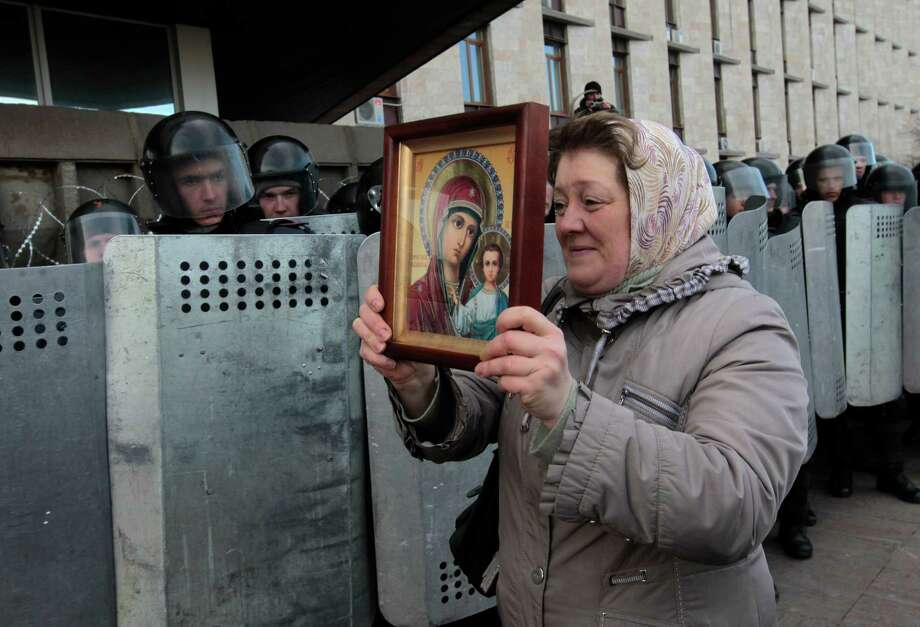 A woman holds up a religious icon as she walks by Ukrainian riot police standing guard at the entrance of the regional administrative building in Donetsk, Ukraine, Saturday, March 8, 2014. Pro Russian activists continued to gather on Saturday in the eastern Ukrainian city of Donetsk, as Russia was reported to be reinforcing its military presence in Crimea. Photo: Sergei Chuzavkov, AP / AP