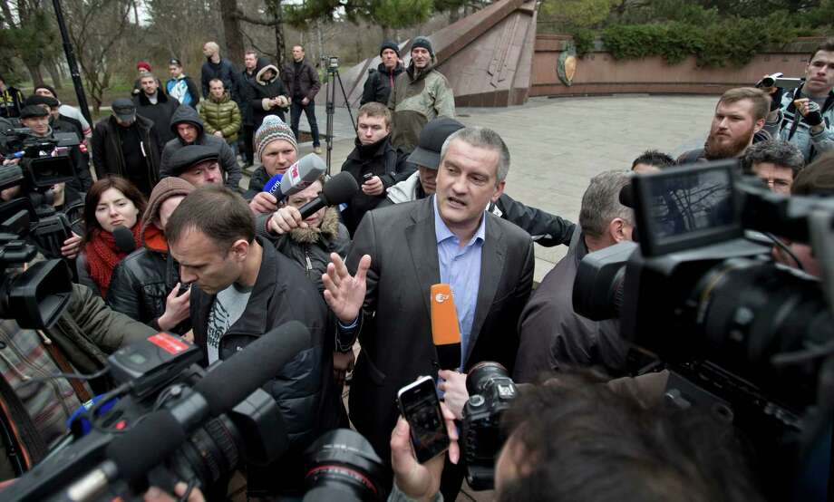 "Crimean Premier Sergei Aksyonov, center, is surrounded by members of the media as he attends the swearing in ceremony for the first unit of a pro-Russian armed force, dubbed the ""military forces of the autonomous republic of Crimea"" in Simferopol, Ukraine, Saturday, March 8, 2014. Some 30 men armed with automatic weapons and another 20 or so unarmed, were sworn in at a park in front of an eternal flame to those killed in World War II. Photo: Vadim Ghirda, AP / AP"