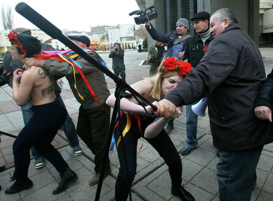 """Femen"" women's rights activists protest against the war in front of parliament building in Simferopol, Ukraine, Thursday, March 6, 2014. Lawmakers in Crimea called a March 16 referendum on whether to break away from Ukraine and join Russia instead, voting unanimously Thursday to declare their preference for doing so. Photo: Sergei Grits, AP / AP2014"