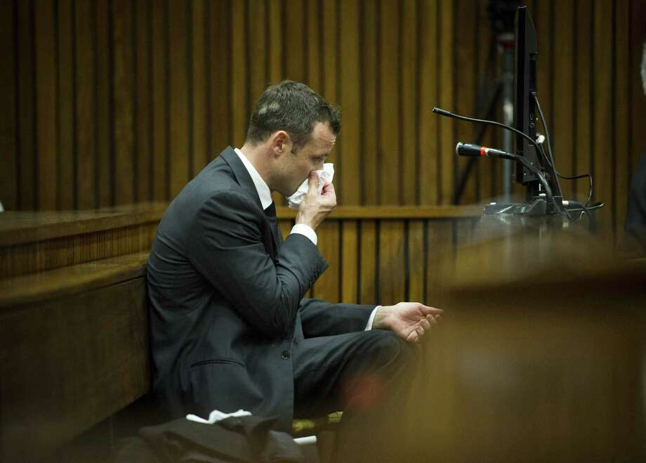 Oscar Pistorius, puts a handkerchief to his face while listening to cross questioning about the events surrounding the shooting death of his girlfriend Reeva Steenkamp, during his trial in Pretoria, South Africa, Friday, March 7, 2014. Pistorius is charged with murder for the shooting death of  Steenkamp, on Valentines Day in 2013.Story: Pistorius trial: Stunning testimony in 1st week Photo: Theana Breugem, AP / AP2014