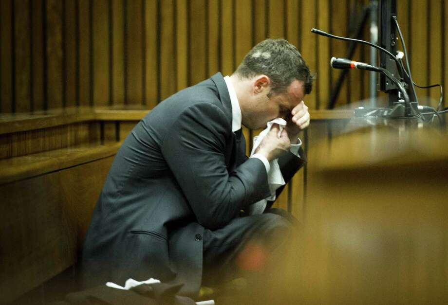 Oscar Pistorius, puts a handkerchief to his face while listening to cross questioning about the events surrounding the shooting death of his girlfriend Reeva Steenkamp, during his trial in Pretoria, South Africa, Friday, March 7, 2014. Pistorius is charged with murder for the shooting death of  Steenkamp, on Valentines Day in 2013.Story: Pistorius trial: Stunning testimony in 1st week Photo: Theana Breugem, AP / MEDIA24