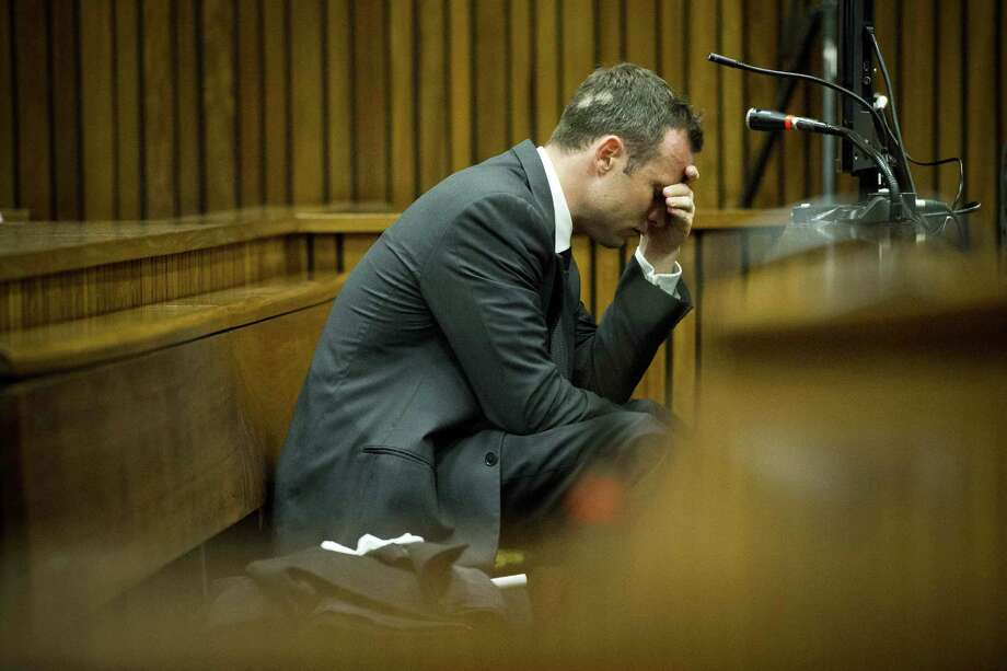 Oscar Pistorius, puts his hand to his head while listening to cross questioning about the events surrounding the shooting death of his girlfriend Reeva Steenkamp, during his trial in Pretoria, South Africa, Friday, March 7, 2014. Pistorius is charged with murder for the shooting death of  Steenkamp, on Valentines Day in 2013.Story: Pistorius trial: Stunning testimony in 1st week Photo: Theana Breugem, AP / AP2014