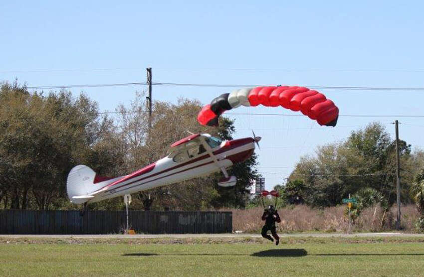 This photo released by the Polk County Sheriff's Office shows a plane getting tangled with a parachutist, Saturday March 8, 2014, at the South Lakeland Airport in Mulberry, Fla. Both the pilot and jumper hospitalized with minor injuries. (AP Photo/Polk County Sheriff's Office, Tim Telford)